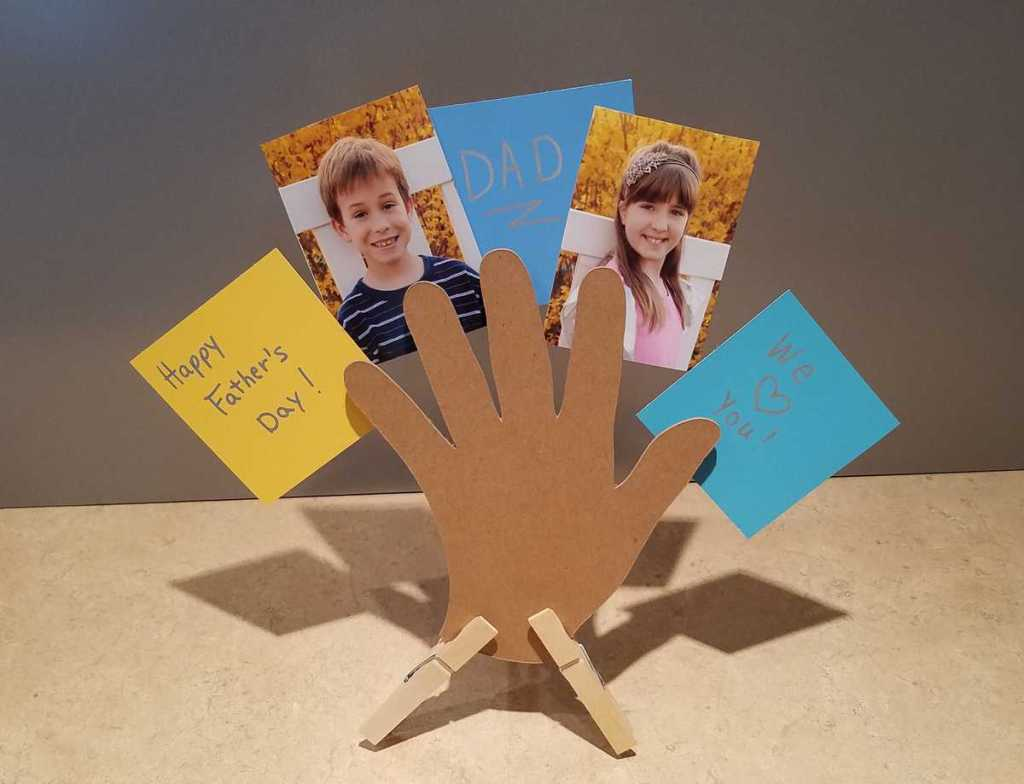 horizontal picture of cut out hand standing on countertop holding children's pictures and notes to dad