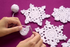 Close-up woman knits crochet Christmas decoration - snowflakes