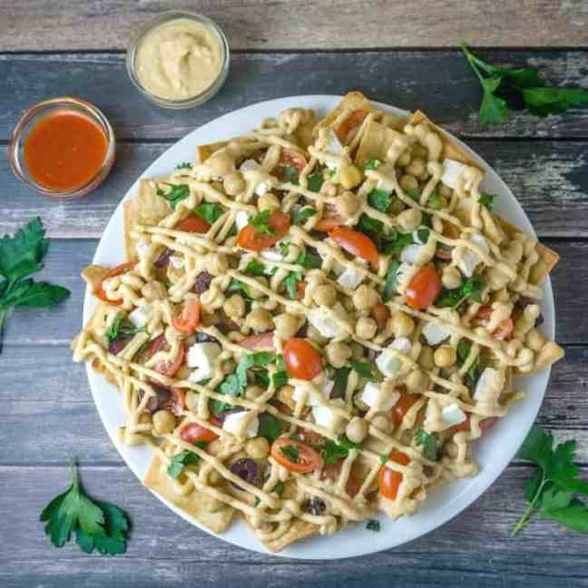 """The Mediterranean Pita """"Nachos"""" are a must-try! All the delicious flavors of the Mediterranean in a delicious platter with heart-healthy chickpeas, feta cheese, fresh veggies and herbs, all topped with a yummy hummus sauce. From http://www.babaganosh.org"""