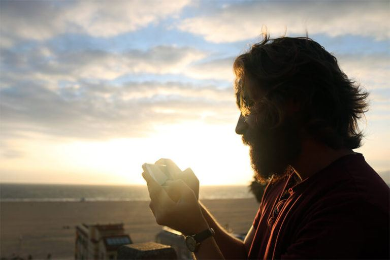 Mann mit Bart steht am Strand und schaut auf sein Handy.
