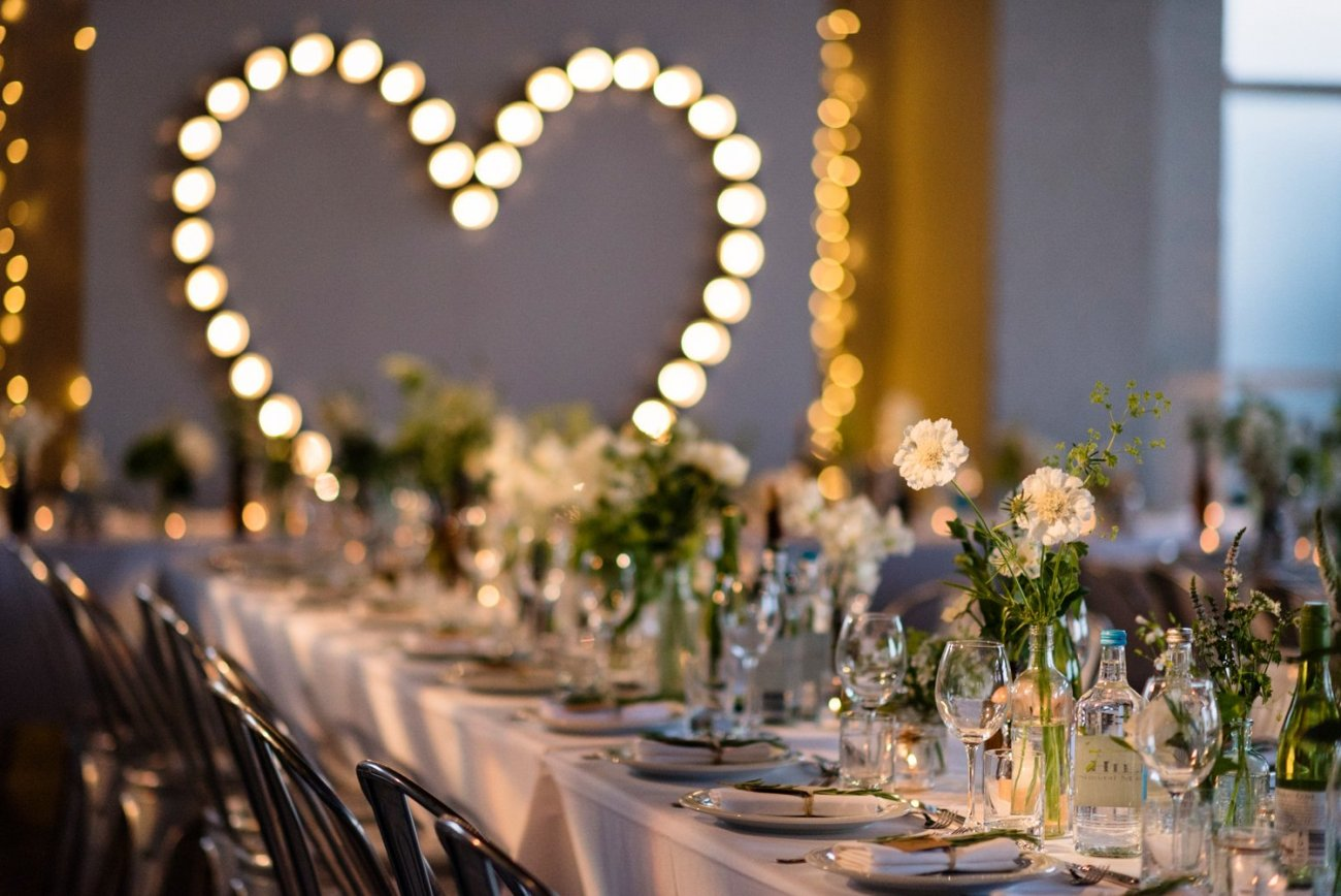 White blooms against heart shaped lights The Chainstore Wedding Photography