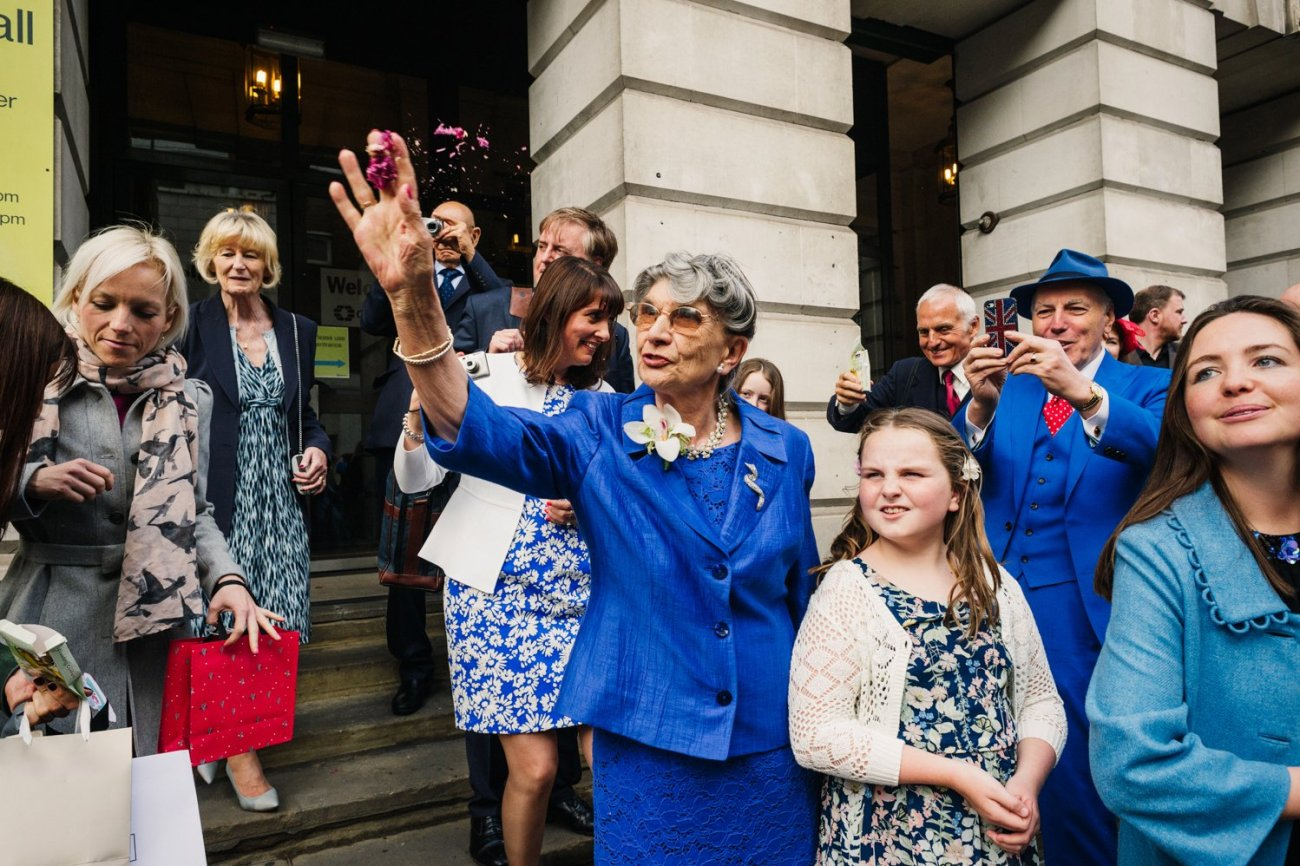 Elderly lady throwing confetti at Camden Town Hall