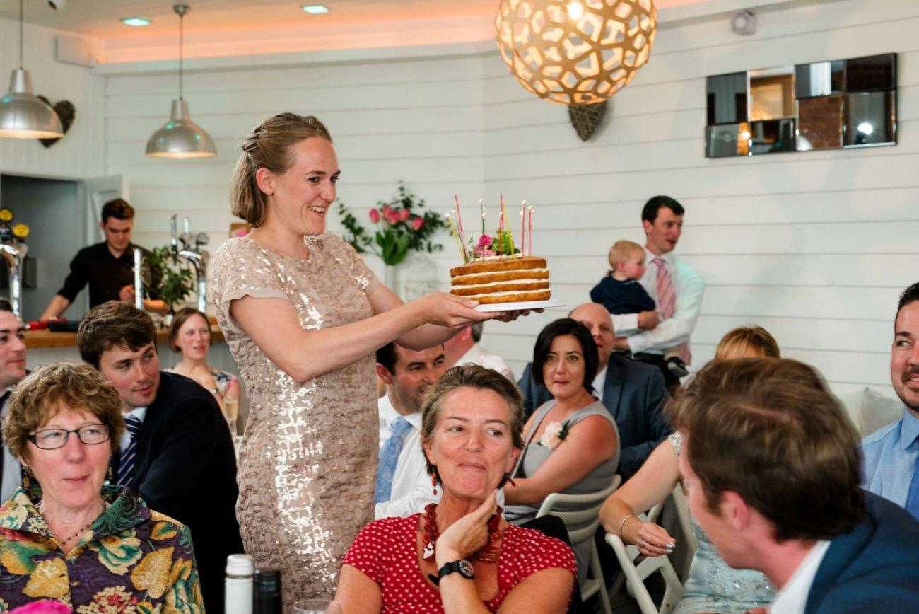 Lady carrying Rosanne Hollowellwedding cake Devon documentary wedding photography