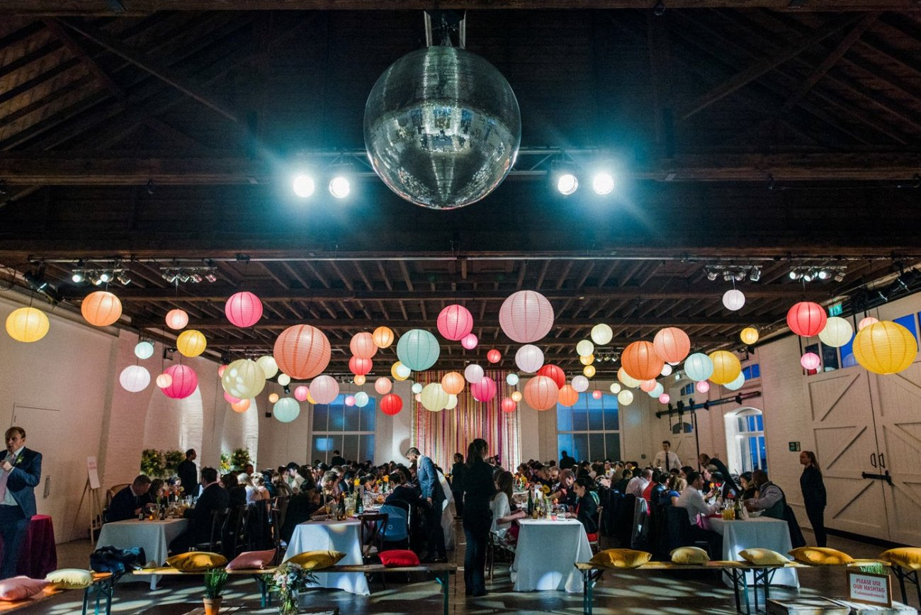 Wedding guests enjoying dinner on large tables at a warehouse wedding in London
