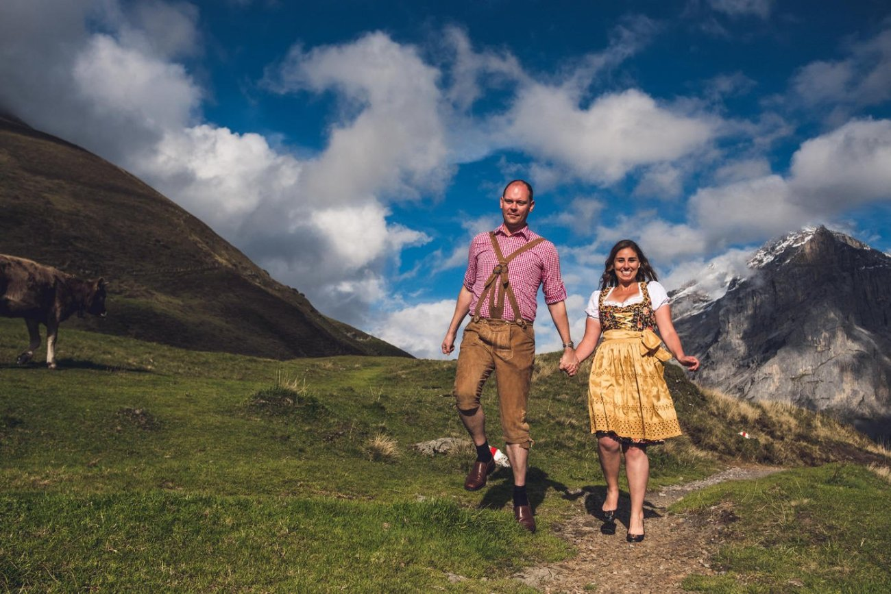 Couple skipping through Swiss alps in dirndl and lederhosen