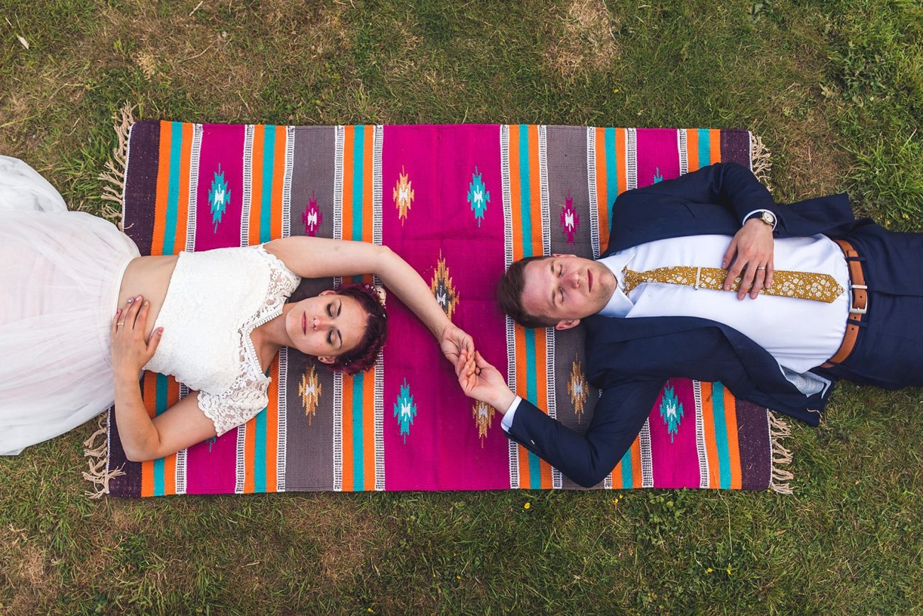 Bride and groom lying on colourful blanket two woods estate wedding