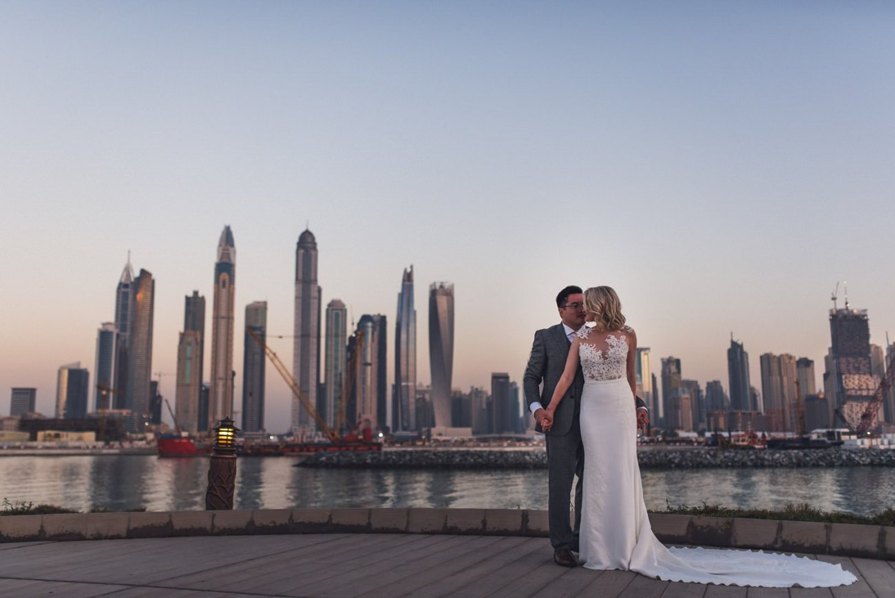 Bride and groom standing in front of Dubai skyline at dusk One and Only The Palm wedding