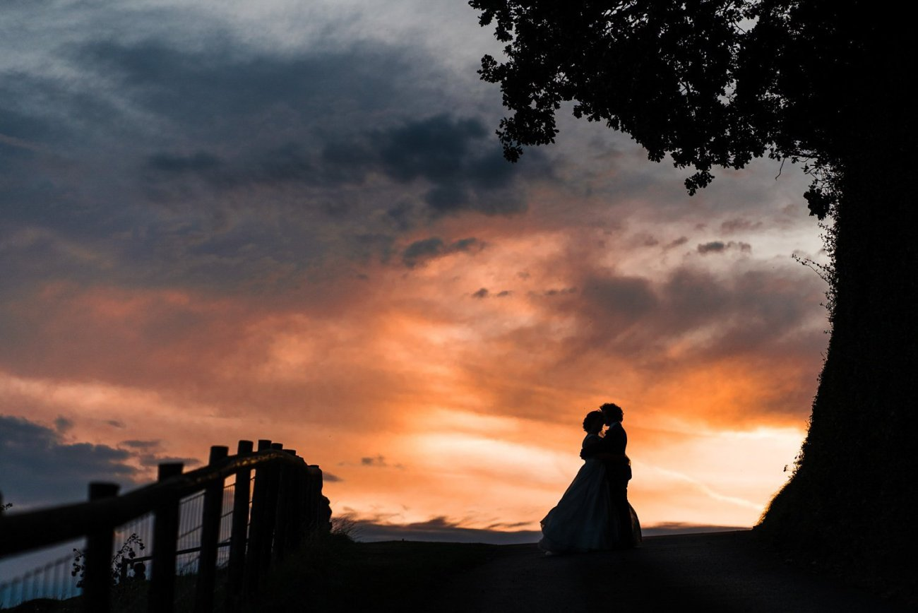 Bride and groom against sunset sky at Kingscote Barn Wedding