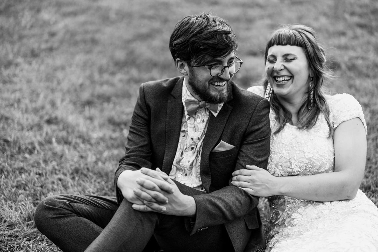 Black and white image of Bride and Groom hugging and laughing in Clissold Park.