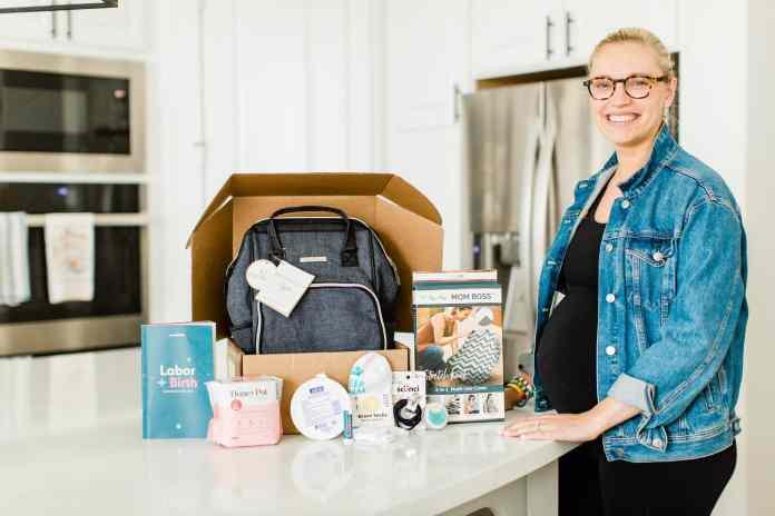 Pregnant woman looking inside the Wumblekin Labor + Birth box.