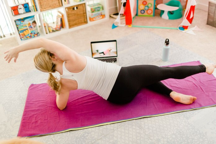 Pregnant woman on her yoga mat looking at her laptop doing a workout in her kids' playroom.