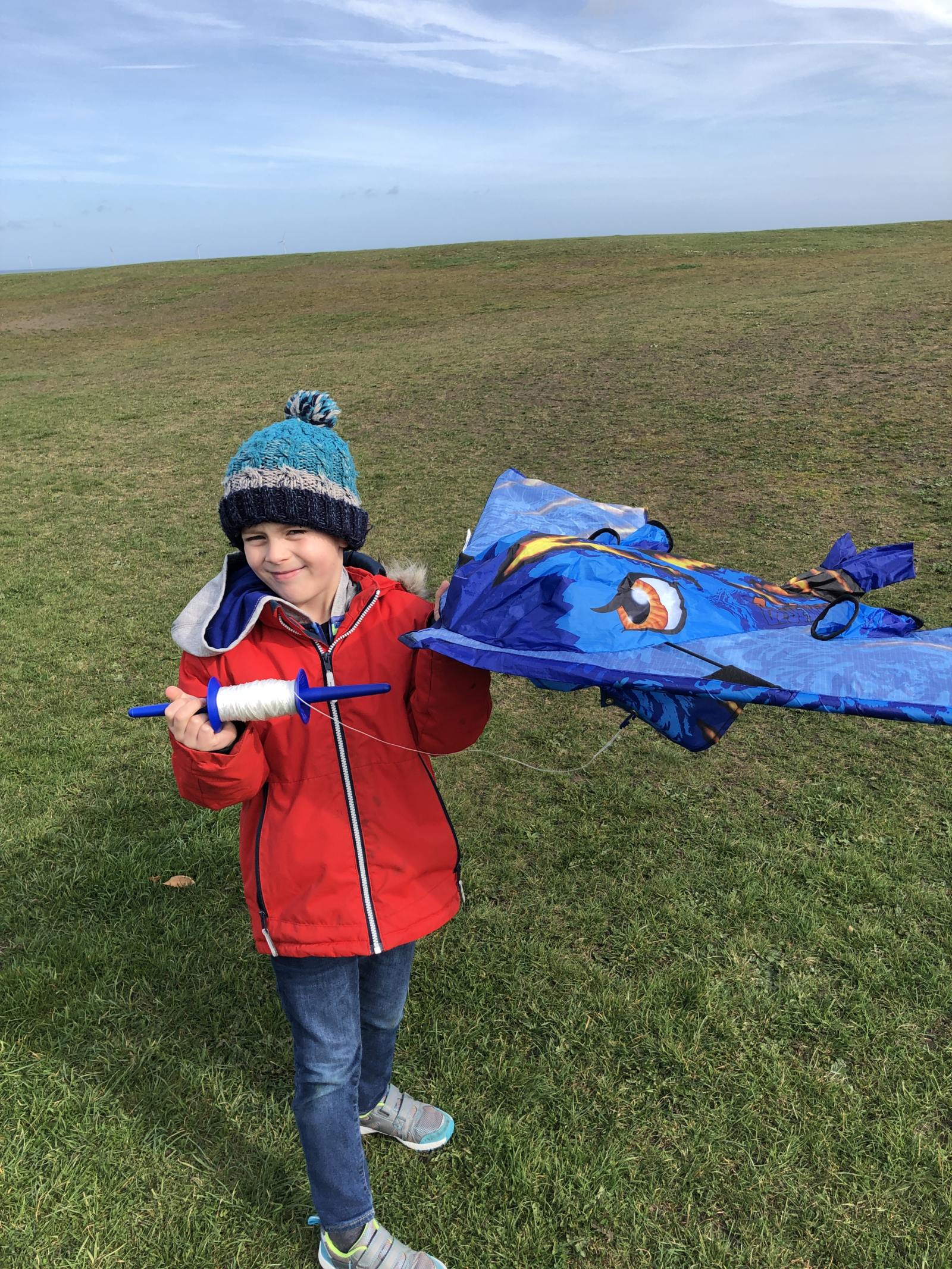 a young boy holding a kitedrone aircraft style kite and string spool