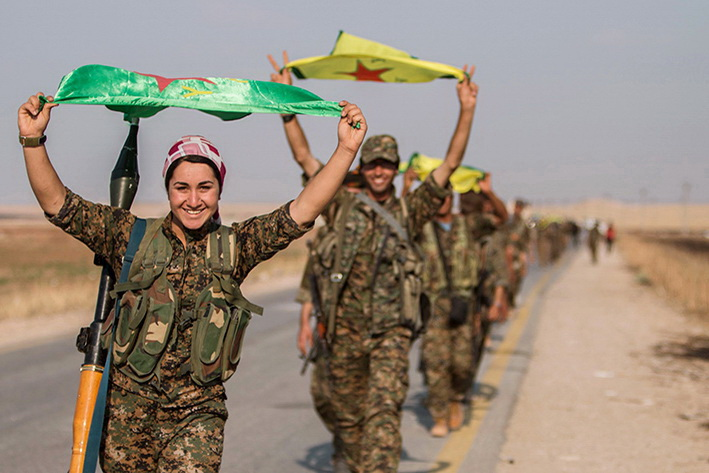 Kurdish fighters gesture while carrying their parties' flags in Tel Abyad of Raqqa governorate after they said they took control of the area