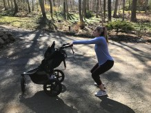 woman squatting with a jogging stroller
