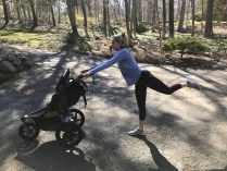 woman holding jogging stroller and kicking behind her