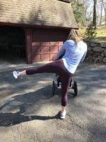 woman with jogging stroller doing a side lunge