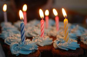 frosted cupcakes with lighted birthday candles