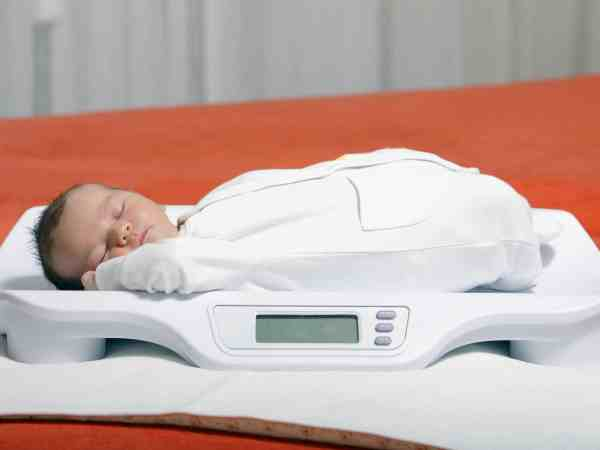 10799772 – baby boy on weight scale