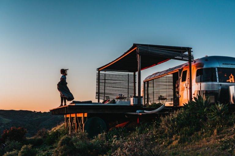 Eine Frau steht an einem Aussichtspunkt, dahinter ist ein Camper parkiert.