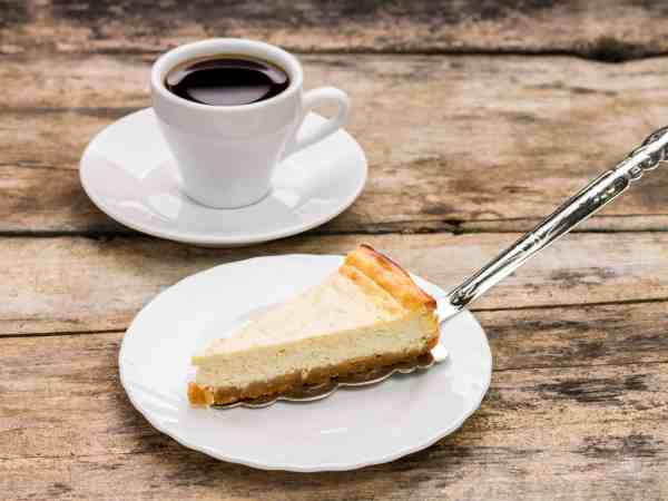 Cheesecake with cake server and cup of coffee on wooden table. desser menu background