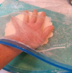 hand in bag between plastic and dough
