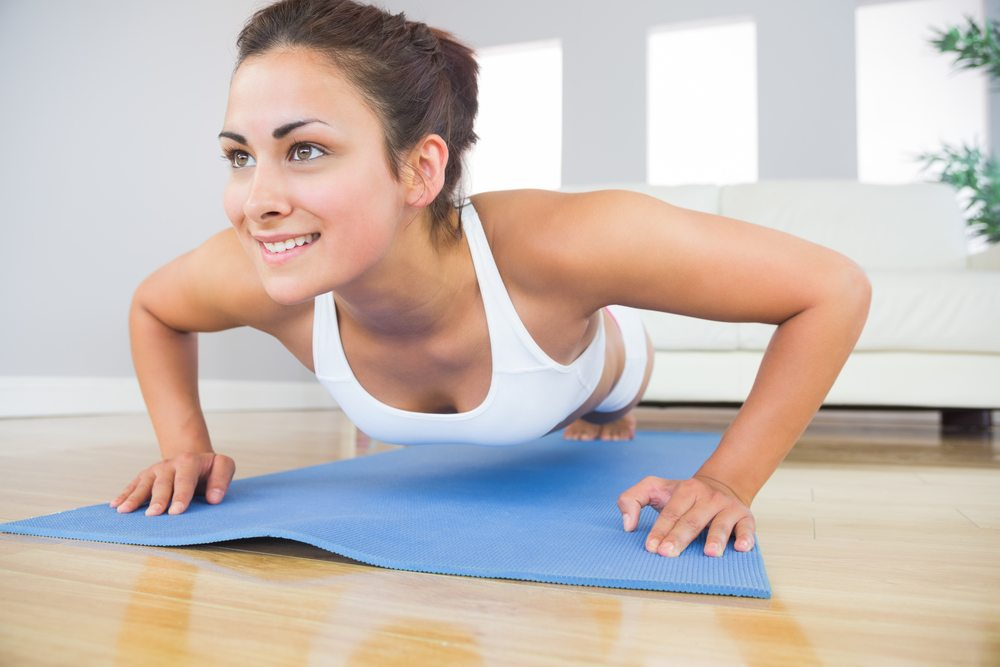 Young Fit Woman Doing Press Ups On An Exercise Mat In Her Living Room