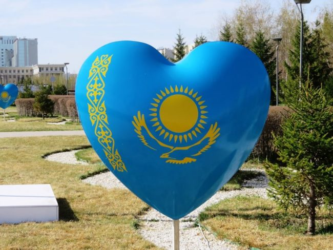 blue heart with the flag of Kazakhstan near the Bayterek tower in Nursultan Astana