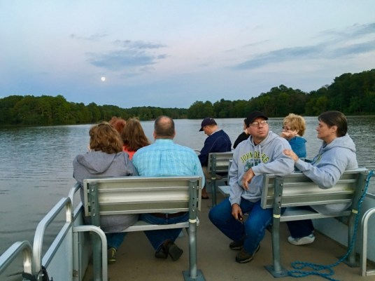 people sitting on a pontoon boat ride