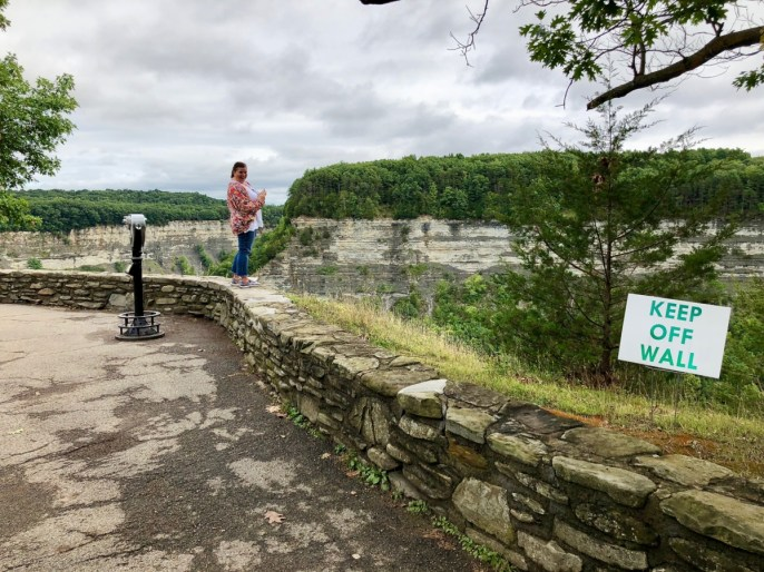 woman ignoring keep off wall sign