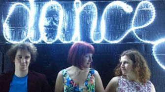 Bugeye band standing in front of illuminated blue sign