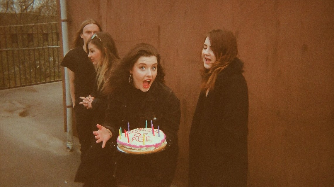 Promo image of The Van T's band holding a cake