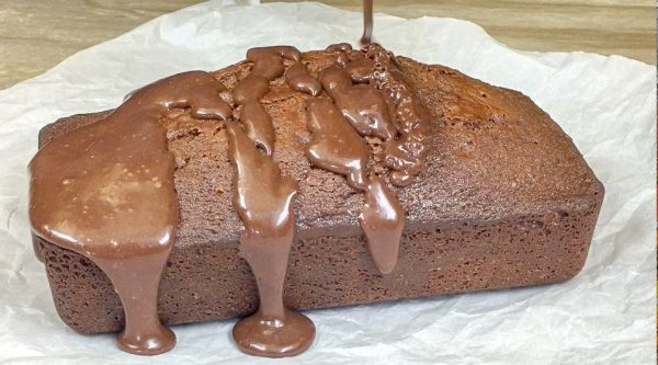 Picture of sweetened condensed milk chocolate pound cake with chocolate frosting being drizzled on the top.