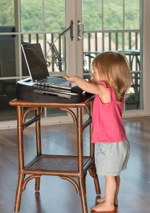 Young baby girl playing with laptop