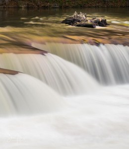 Heavily flooded Tygart Valley river flows in smooth slow motion image over waterfall in Valley Falls State Park West Virginia