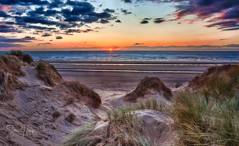 Sun setting over the beach at Formby in England through sand dunes