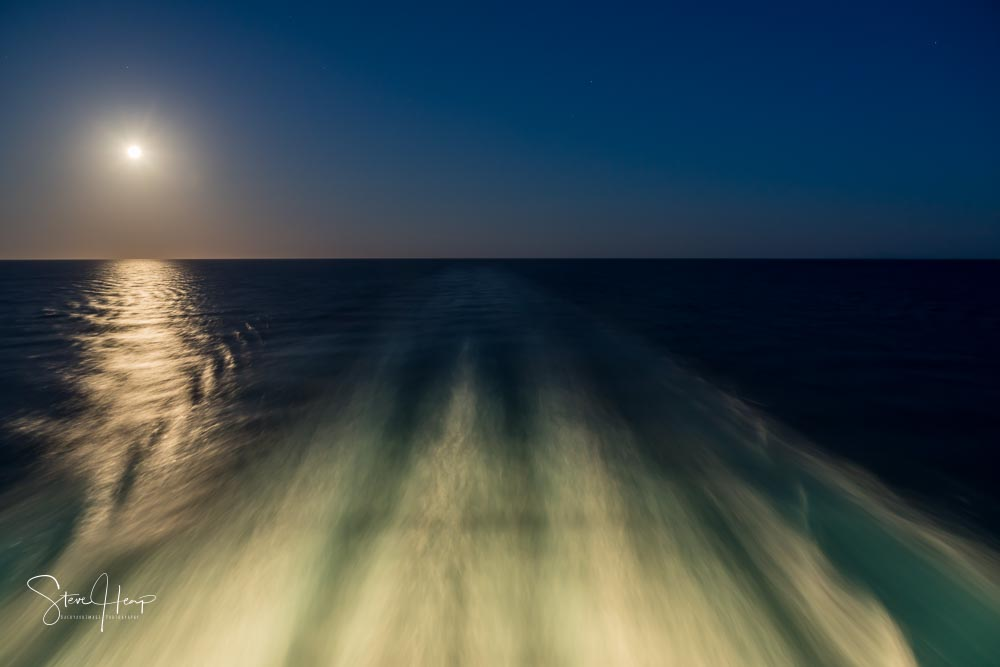 Moon over the wake of a cruise ship at night with the moon on the horizon stock photo