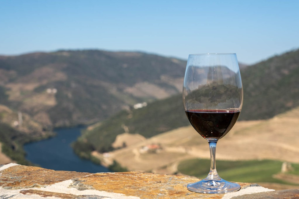 Red wine on stone wall overlooking the Douro valley and river with vineyards on the hillsides