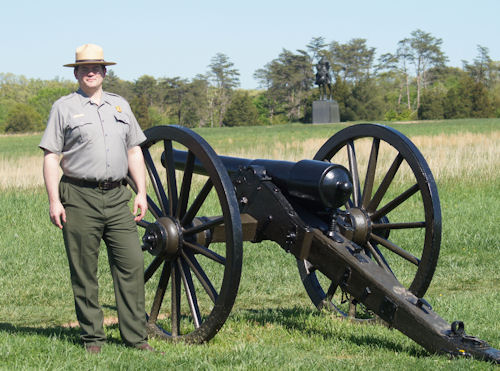 Manassas Battlefield Park Superintendent Ed Clark stands by a federal cannon with a statute of Stonewall Jackson in the background.