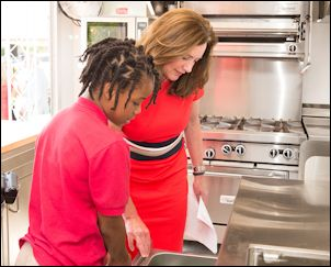 First Lady Dorothy McAulliffe and a student from St. Andrew's School check out the Class-A-Roll kitchen.