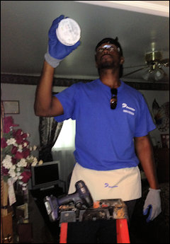 Terrence Moore, a customer project designer for Dominion, was one of a half dozen volunteers who took the day Thursday to weatherize Mary Jones's House. Here, Moore installs a carbon-monoxide monitor.