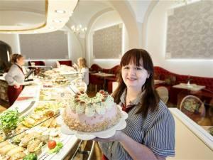 Fanny Ginge präsentiert das Tortenangebot im frisch sanierten Café Wittig auf dem Obermarkt