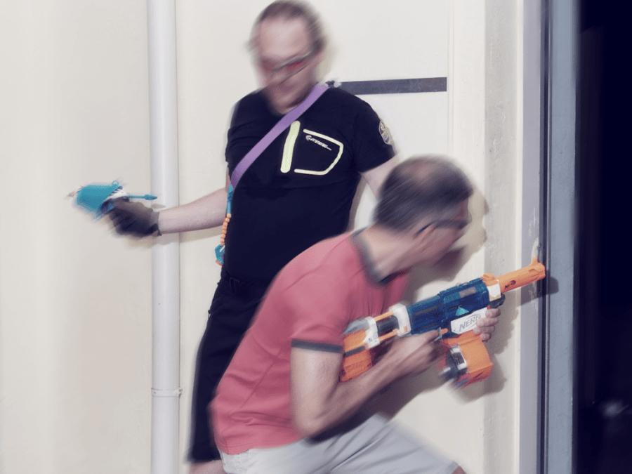 Zwei ältere Nerf Spieler im begriff durch eine Tür zu rennen.