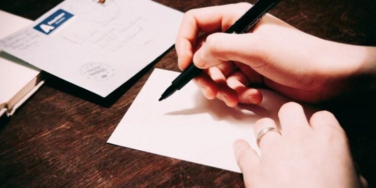 Woman writing postcard