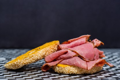 Open smoked meat sliced and placed aesthetically in a sesame bagel