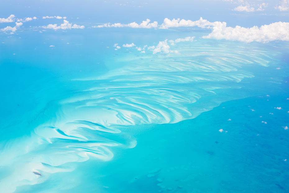 Aerial view of the Bahamas, stunning islands, sand bars and coral reefs with turquoise sea, shot from aeroplane. Check out this Miami to Bahamas flight on a Bahamas charter you've always dreamed of. Imagine yourself on one of our flights from Miami to Nassau or other flights to Bahamas ready to enter paradise. Our Florida to Bahamas flights are one of the best day trips in Florida. Bahamas Air Tours gives you your guide to Day Trips to Bahamas by flights to Bahamas aboard Bahamas Air Charters to Swimming Pigs tours and the Exuma pigs on Pig Island at Pig Beach. Join one of our Staniel Cay Day trips on our Nassau to Staniel Cay day tour or opt for the Staniel Cay Day trips by the way of Bahamas Day Trips by plane. Trips to Bahamas to see pigs in Bahamas. Miami to Bahamas day trip is one of the top Florida attractions.