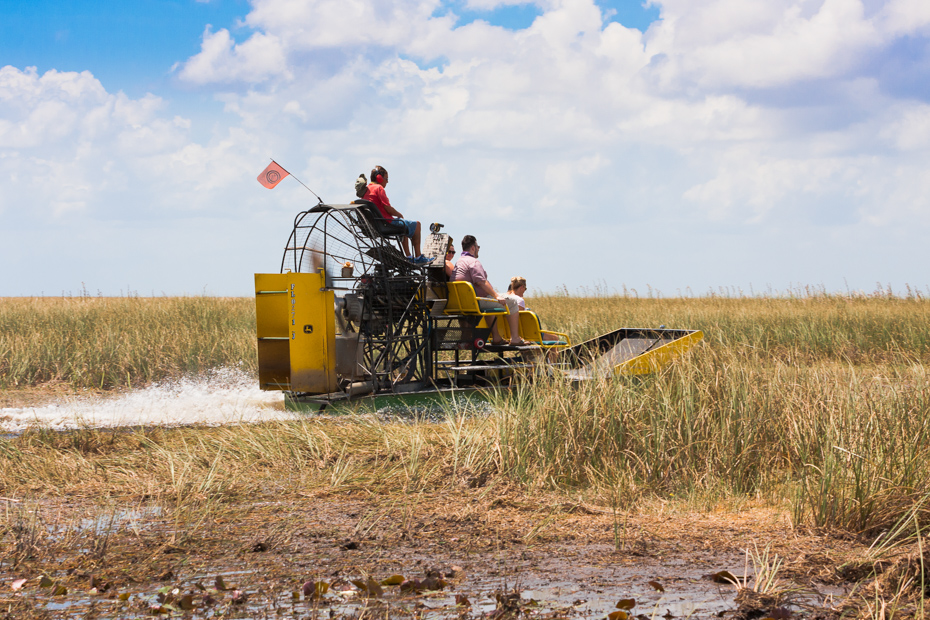 Group of tourists riding an airboat in Everglades National Park. All aboard Florida Airboat tours and Airboat rides Florida through Everglades Airboat tours and the best things to do in Florida.