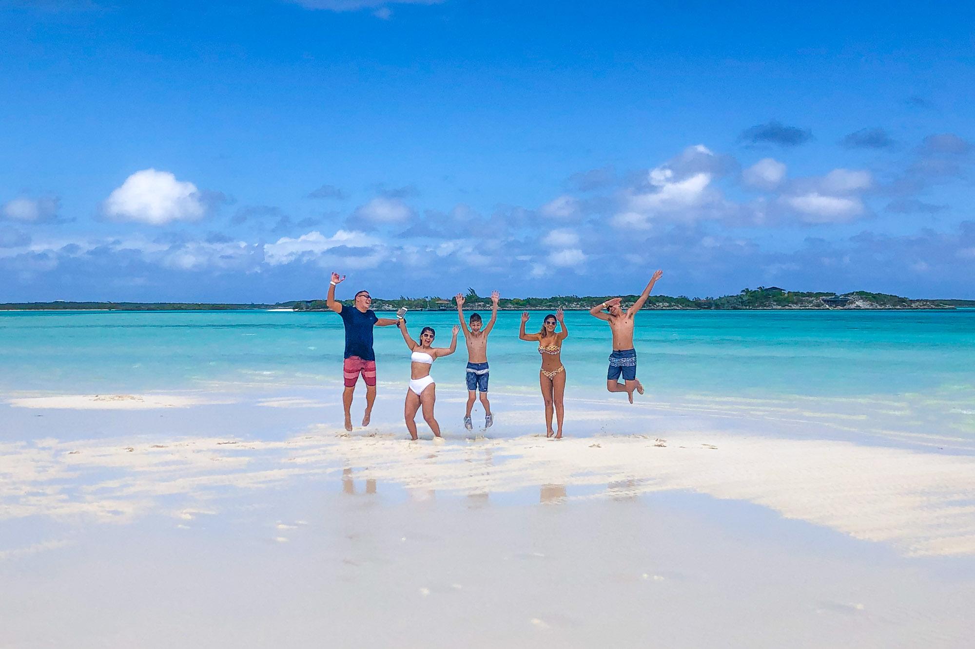 Family enjoying the Exuma Cays Sand Bar at Pipe Creek close to Staniel Cay Exuma Bahamas.