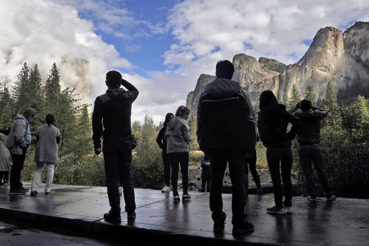 Visitors to Yosemite Valley view clouds forming along the granite ridges after a rain storm in California's Yosemite National Park. Photographer: Eric Paul Zamora/Fresno Bee/TNS via Getty Images