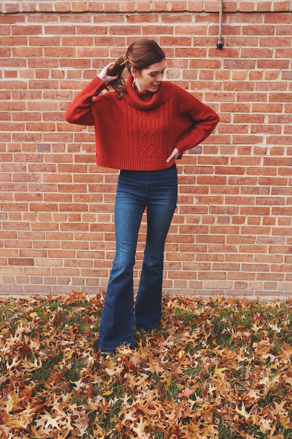 girl against brick wall wearing flare jeans and orange sweater for thanksgiving