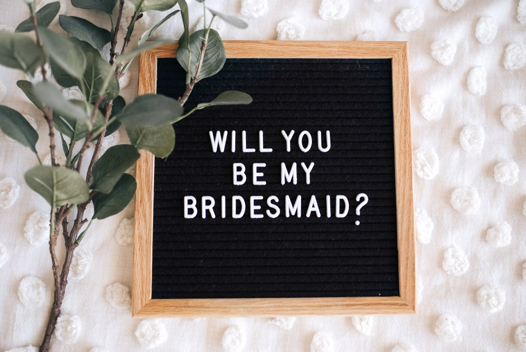 """will you be my bridesmaids?"" written out on a letterboard"
